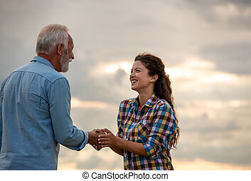 Young woman shaking hands with senior man