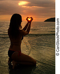 Young woman shaping heart with her hands at sunset, Langkawi island, Malaysia, Southeast Asia
