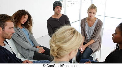 Young woman sharing her problems in group therapy