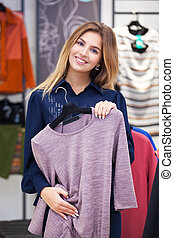 Young woman shopping and looking at some clothing in a...