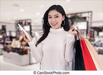 woman shopping and using digital tablet at mall