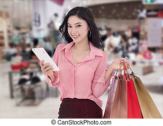 young woman shopping and using digital tablet at mall