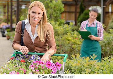 Young woman shopping  flowers in garden center