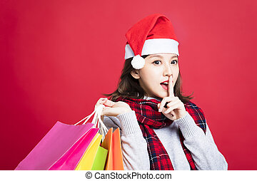 young Woman shopping for christmas gifts with secret gesture