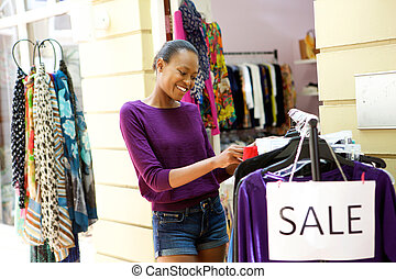 Young woman shopping for clothes at store