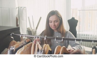 Young woman shopping for clothes fashion designer browsing wardrobe.
