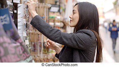 Young woman shopping for sunglasses standing in front of a...
