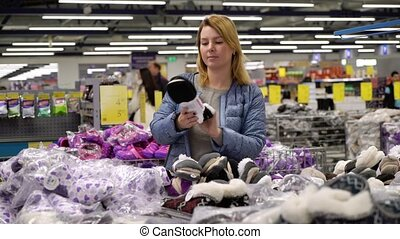 Young woman shopping in hypermarket. Choosing shoes in a...