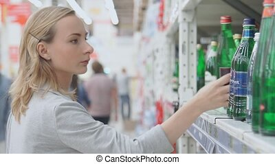 Young woman shopping in the supermarket. She choosing a bottle of mineral water and putting it in her shopping basket.