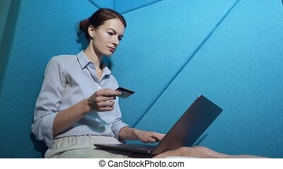 Young woman shopping online with credit card on laptop.