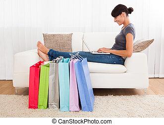 Young Woman Shopping Online - Young Beautiful Woman Sitting...
