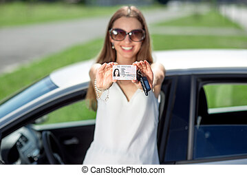 Young woman showing a key and license in front of the car....