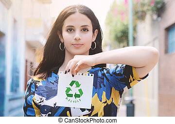 Young woman showing a notepad with recycling symbol