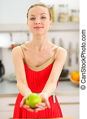 Young woman showing apple