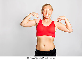 Young woman showing biceps