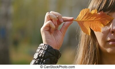 Young woman showing colorful autumn leaves to the camera. Beautiful woman holding autumn yellow leaf near face. Autumn sadness. Slow motion