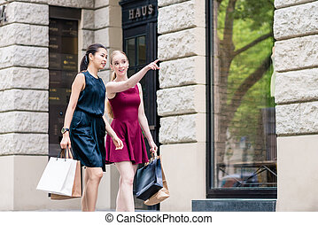 Young woman showing direction to her friend during shopping session