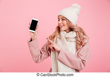 Young woman showing display of phone pointing.