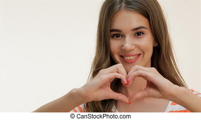 Young woman showing heart shape gesture