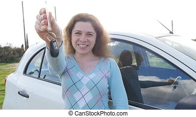 Young woman showing key to a new car
