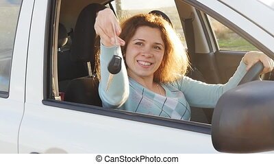 Young woman showing key to new car
