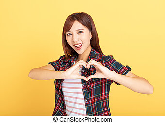 young woman showing love with hands in heart shape