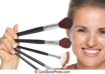 Young woman showing makeup brushes