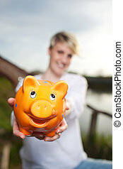 Young Woman Showing Piggy Bank Outdoors