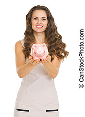 Young woman showing piggy bank