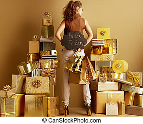 young woman showing shopping bags and Black Friday sign