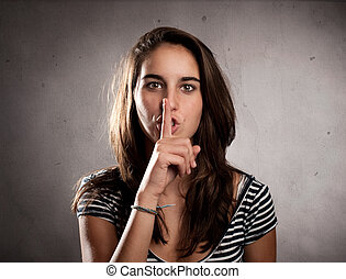 young woman showing silence gesture