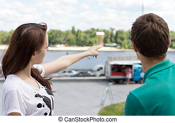 Young woman showing the direction to a tourist