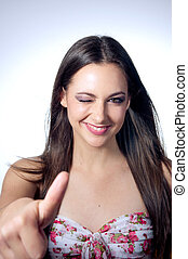 young woman showing thumb up and smiles