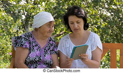 Young woman shows her elderly mother how to use the tablet.