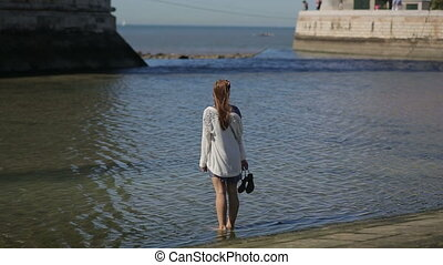 Young woman sightseeing, walking shoeless in water at harbour front of the ocean