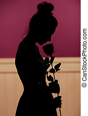 Young woman silhouette holding flower