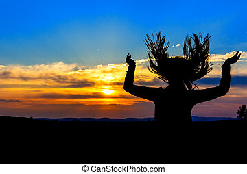 Young woman silhouette in the sunset