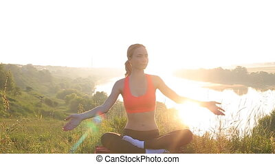 Young woman silhouette practicing yoga at sunset.