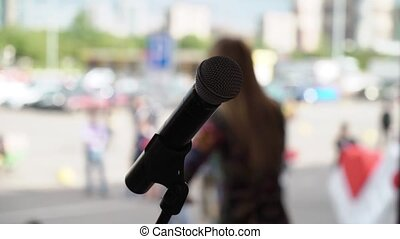 Young woman singer at stage on concert outdoors open-air...