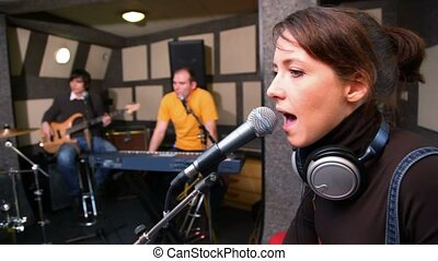 young woman singing in studio, musicians in background