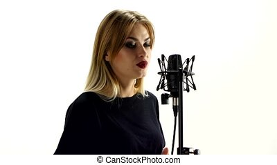 Young woman singing with studio microphone. Isolated on white background.