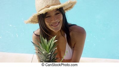 Young woman sipping a pineapple cocktail