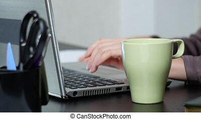 Young woman sipping tea on laptop while working in office....