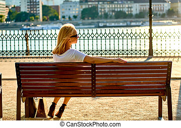Young woman siting on a bench on the riverside - A beautiful...