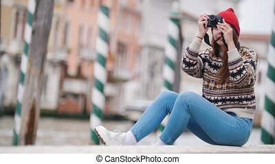Young woman sits by the river and takes interesting photo -...