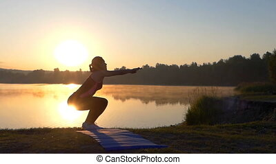 Young woman sits down on a lake bank at sunset