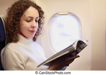 Young woman sits in a chair near the illuminator of the airplane and reads the magazine.