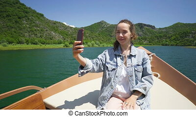 young woman sits in a motorboat and makes a video call on a...