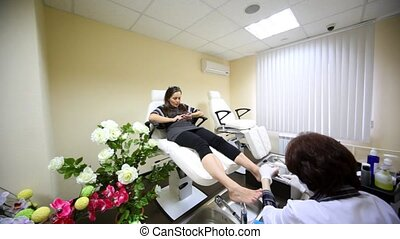 Young woman sits in armchair for pedicure near to flowers -...
