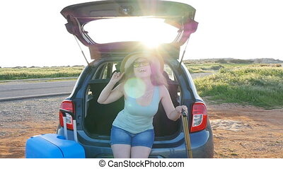 Young woman sits in the trunk of a car. Travel concept